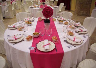 Mesa comunión con mantel blanco y camino fucsia